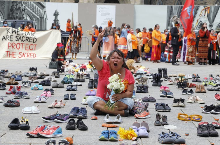 Woman sits with fist in the air, wearing orange t-shirt, holding teddy bear, surrounded by hundreds of little shoes
