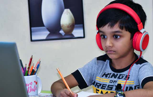 A boy in headphones looking at a laptop with a pencil.