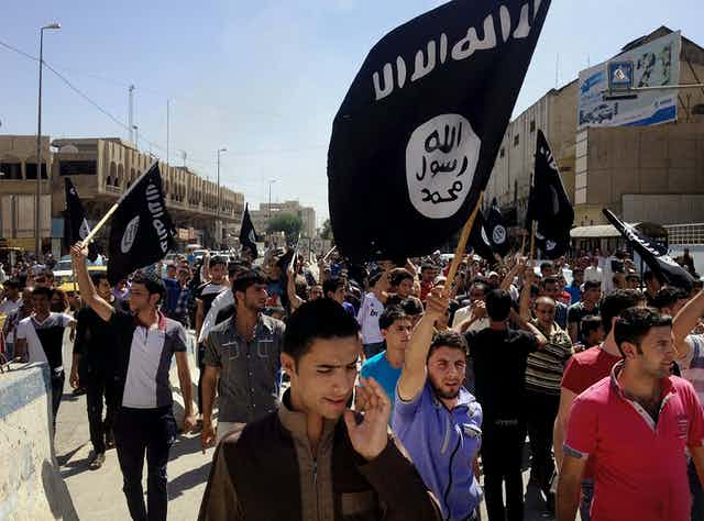 A crowd of people fill a street waving black Islamic State group flags.