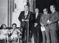 A man speaks on stage next to two Black children and a group of other men.
