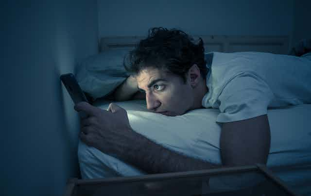 Man lays in bed with the lights off, the glow of his cellphone illuminates his face