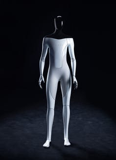A humanoid robot with a black head and shoulders and white body with the name Tesla across its chest