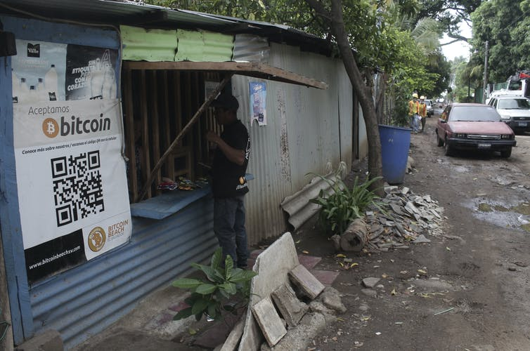 A man in Tamanique, El Salvador, makes a purchase at the opening of a small store that has a sign that says it accepts bitcoin.