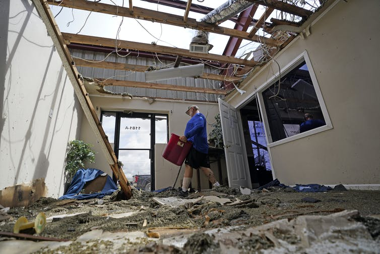 A man walks through the debris of an office with the roof torn off.