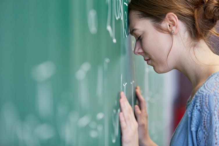 Tired teacher leaning head against blackboard.