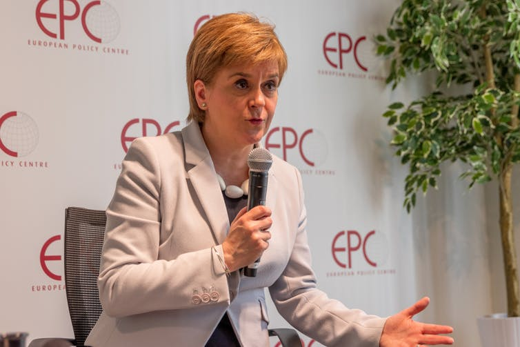 Scotland's first minister Nicola Sturgeon in a cream jacket holding a microphone.