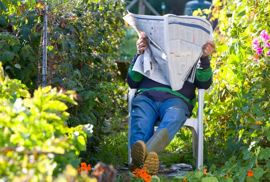 A man sitting in his garden reading a newspaper