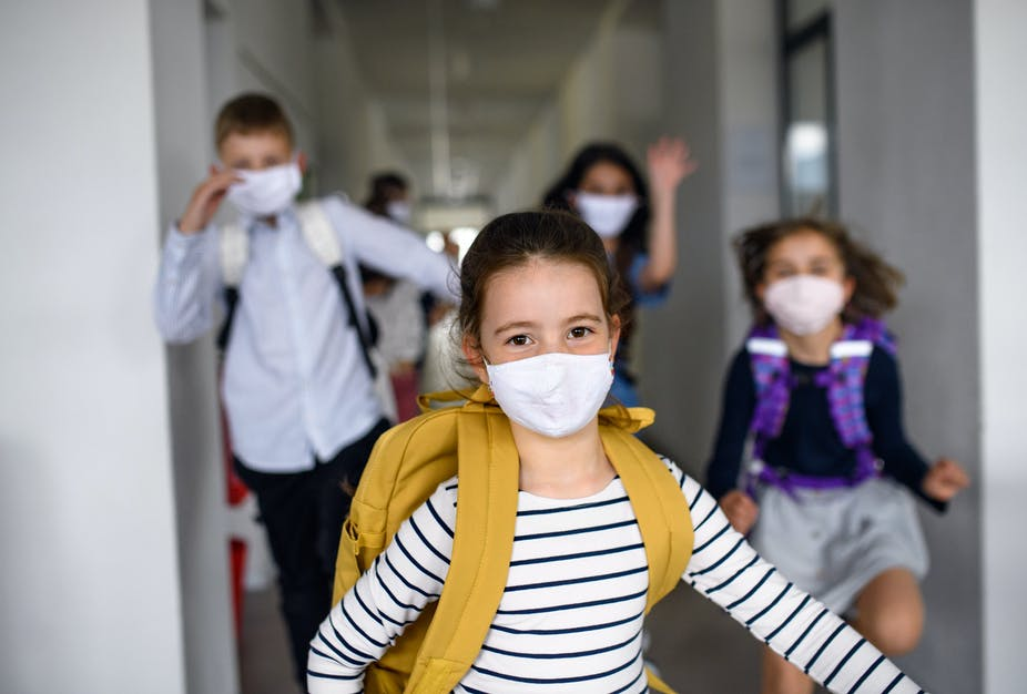 A group of children with masks on.