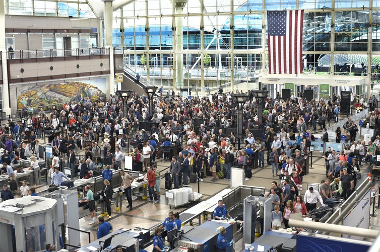 A sea of people in an airport waiting in line to pass through TSA security