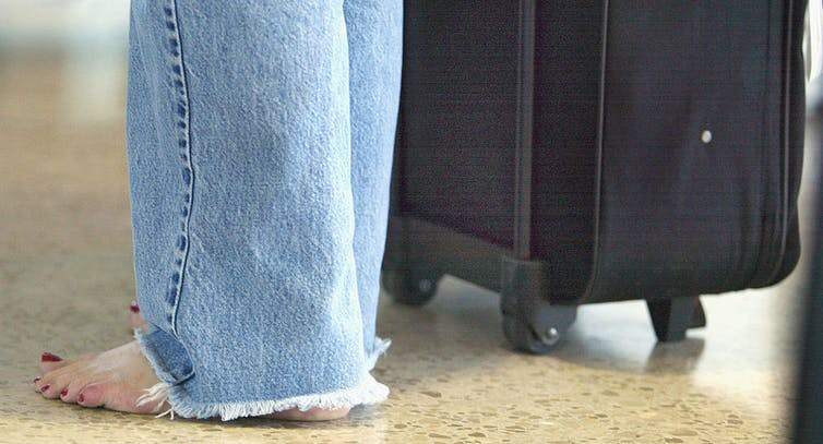 Barefoot woman stands next to her luggage.