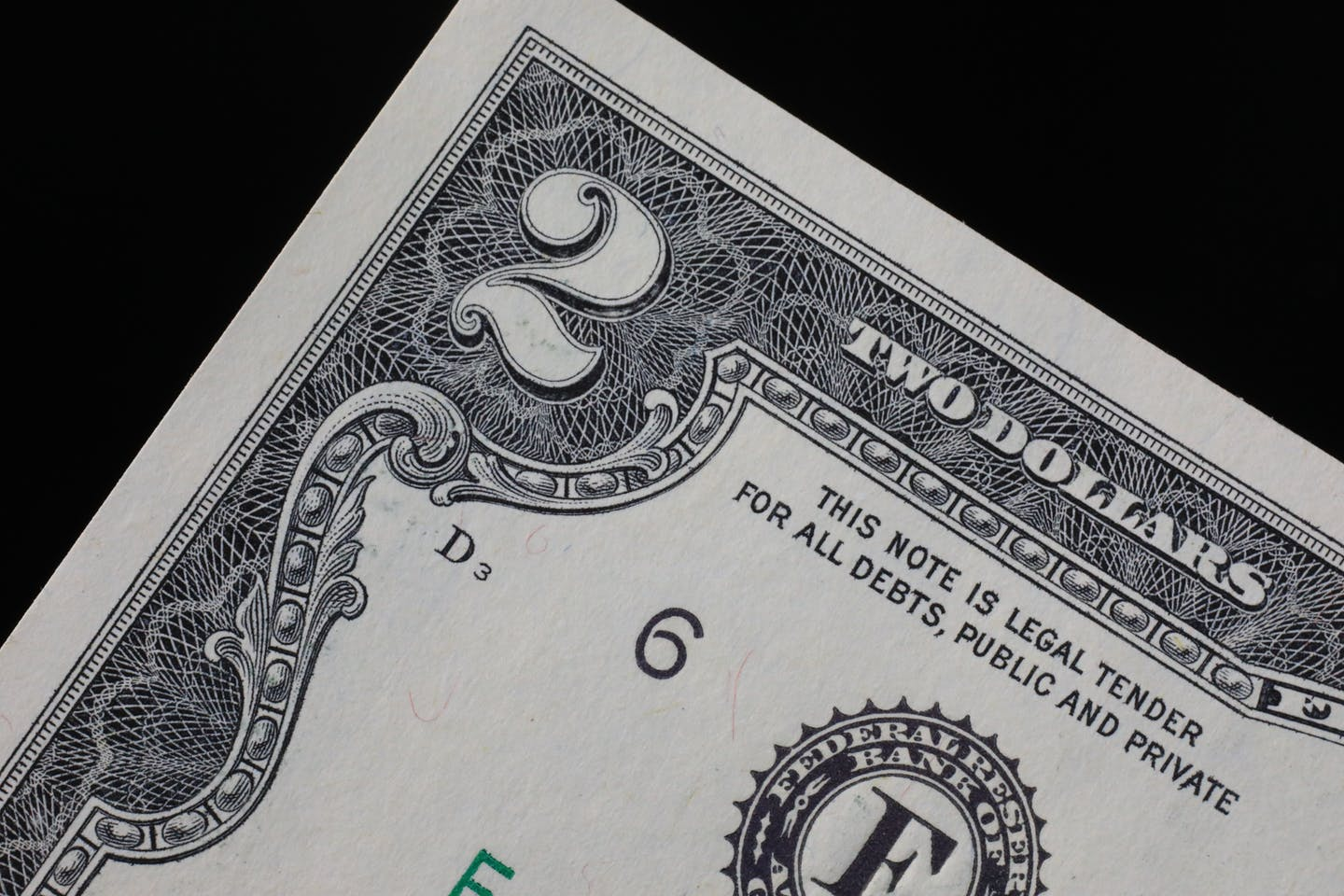 A closeup of the $2 bill and the words 'this note is legal tender for all debts, public and private'