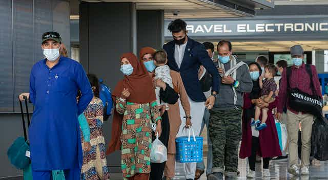 Refugees from Afghanistan walk through a U.S. airport.