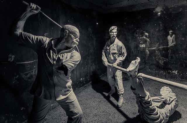 An image of a museum exhibit depicting people torturing a person