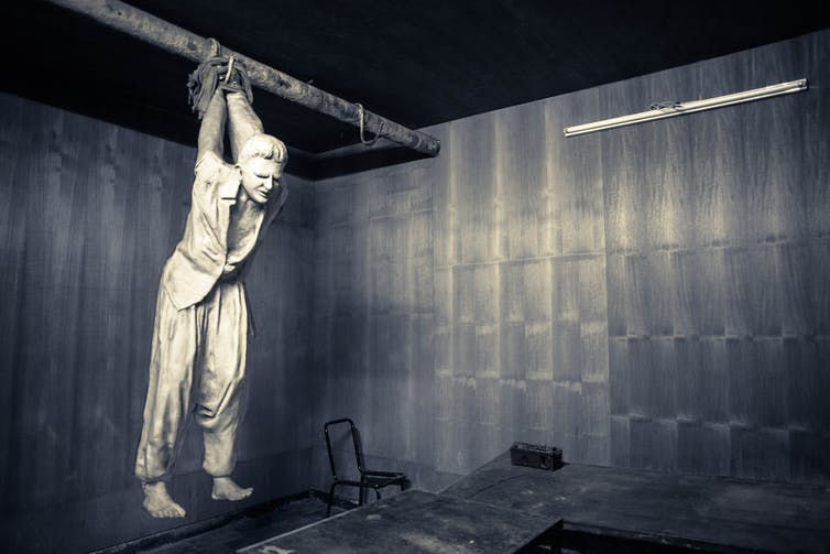 A figure of a person suspended by the arms from a bar across a room, with their feet unable to reach the ground.