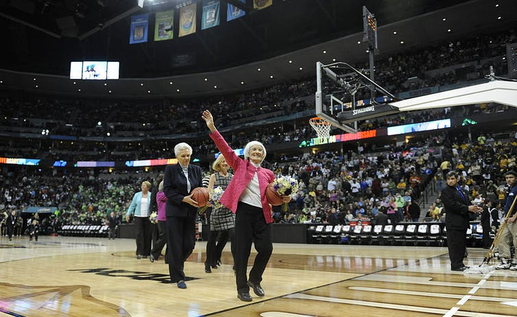 Bernice Sandler waves at people in the stands on a basketball court