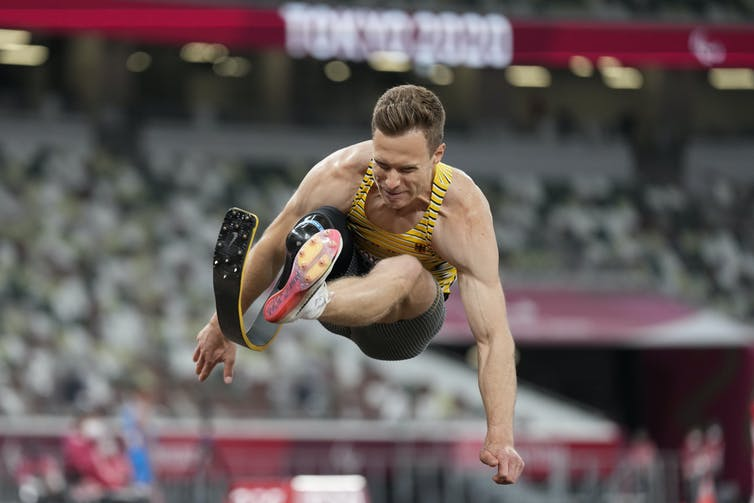 Athlete with blade prosthetic in the middle of long jumping