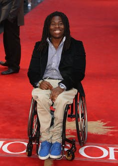 Man sitting in a wheelchair on a red carpet