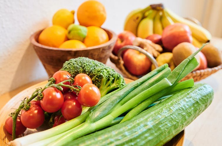 Bowls of oranges, bananas, tomatoes, scallions and other produce are attractively arrayed.