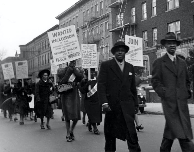 Black members of the Domestic Workers Union Members march down a road in protest.