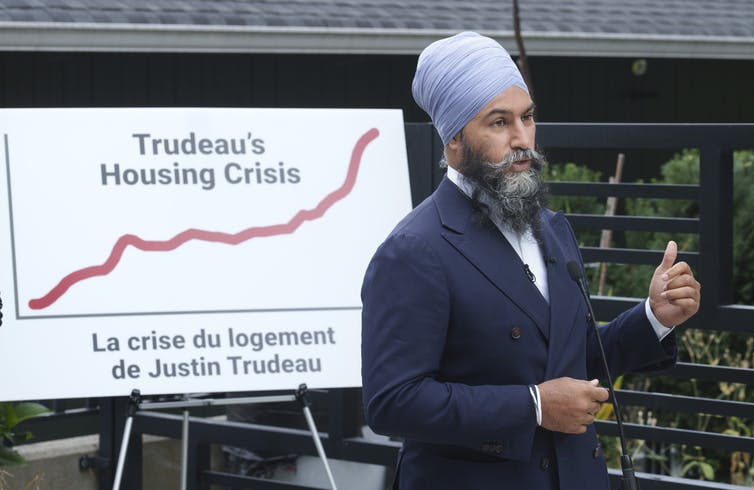Jagmeet Sing stands in front of a sign that reads 'Trudeau's Housing Crisis'
