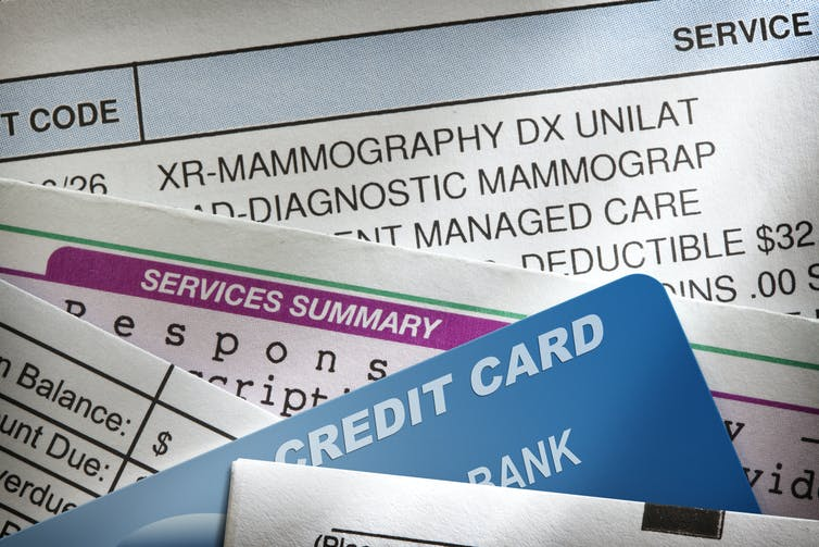 Medical bills stacked on top of each other with a credit card nestled between forms.