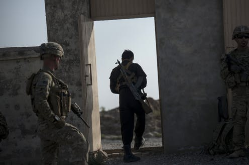 Un policía afgano y soldados estadounidenses salen de una escuela