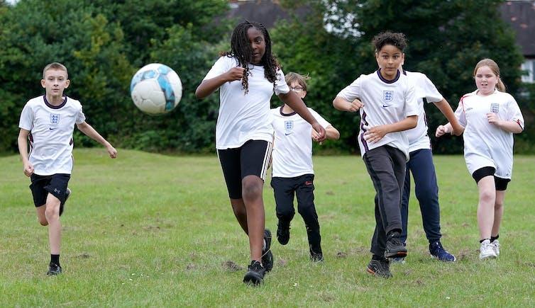 Boys play football on a green field
