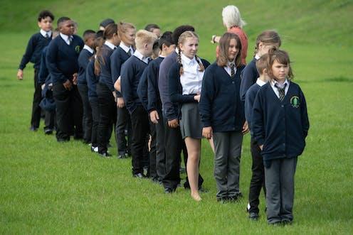 Children in school uniform queue on a playing field