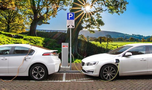 Two white electric cars charge in the sunshine