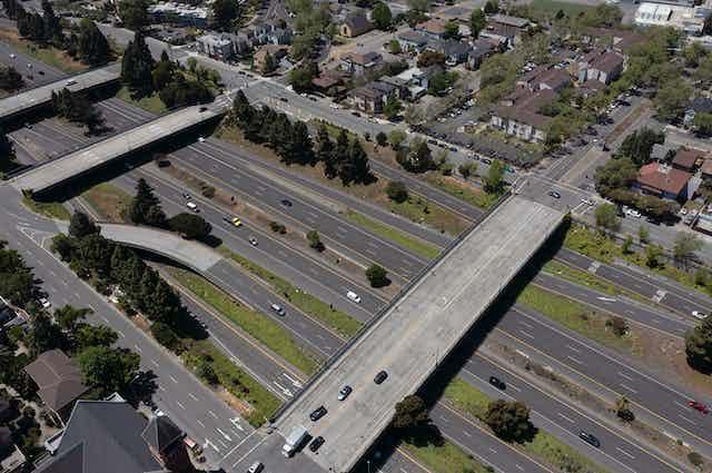 Highway with overpasses dividing neighborhoods.