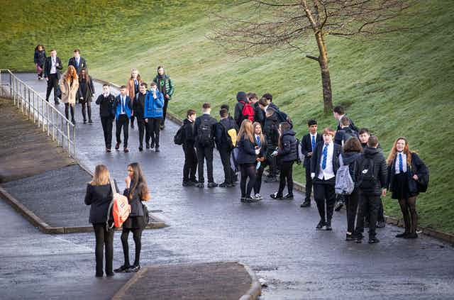 Secondary school students stand in small groups near a green field