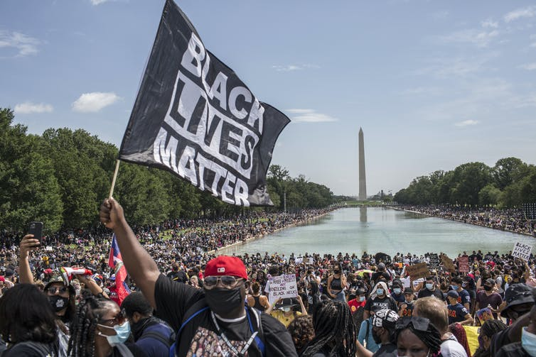 A demonstrator holds a flag with Black Lives Matter written on it at a protest at the Lincoln Memorial in Washington, D.C.