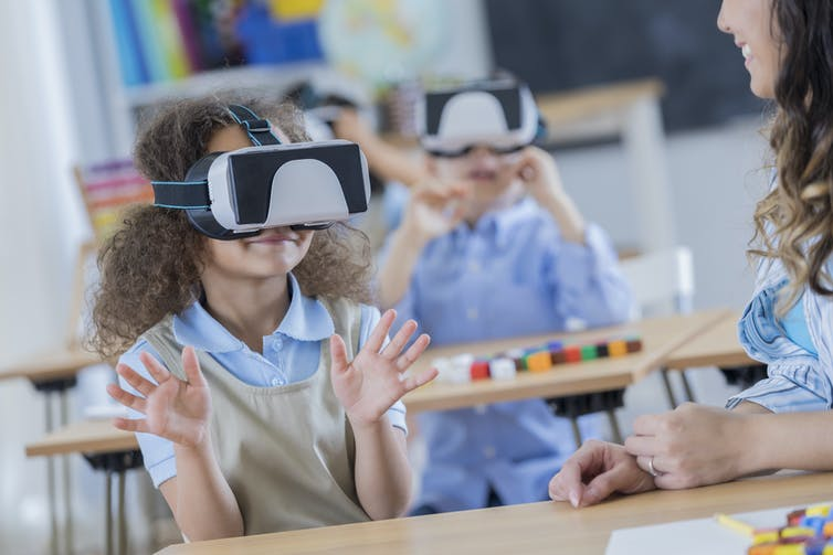 A group of young girls wear VR headsets in class.