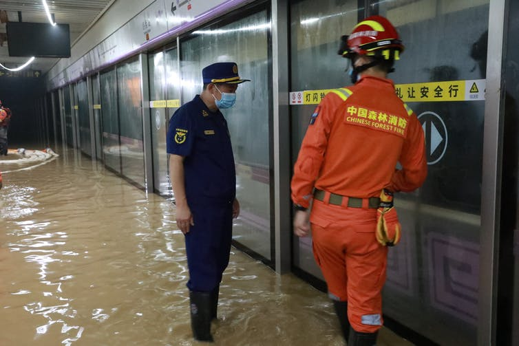 Firefighters pump rainwater from a flooded metro station in Zhengzhou, China
