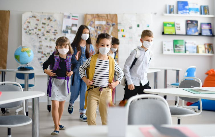 Masked children enter a primary school classroom
