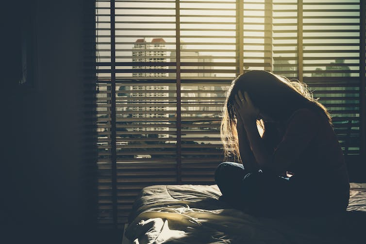A woman sits on a bed in the dark, appears depressed.