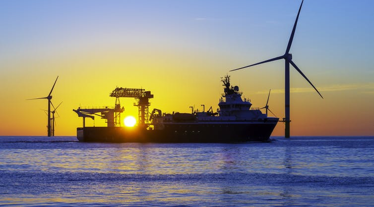 A ship outside turbines at sunset