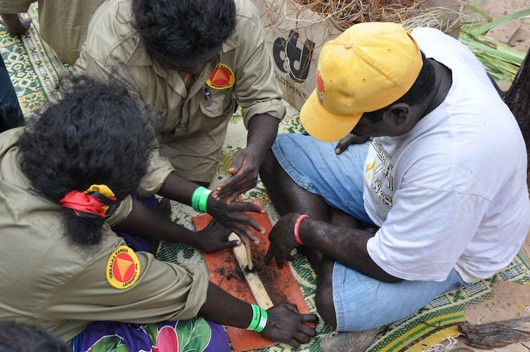 Dhimarru Indigenous Rangers teaching traditional fire making at Garma Festival.