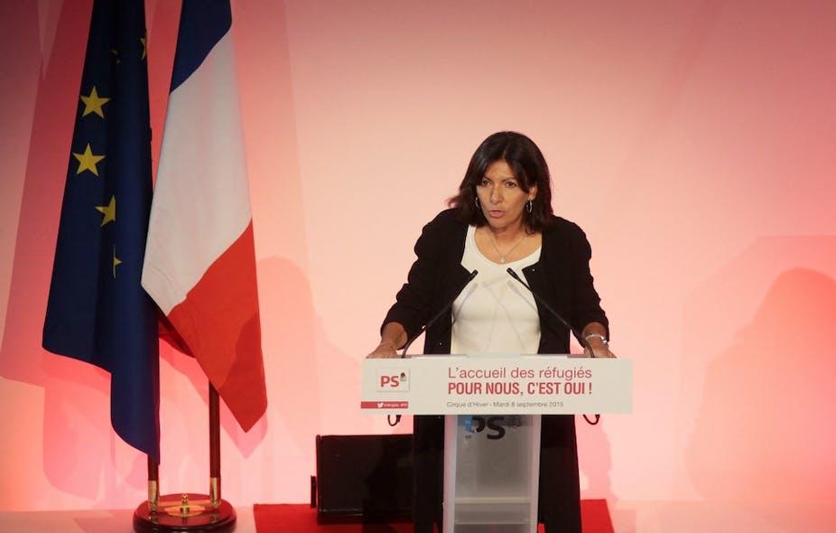 Femme politique en plein discours, en tribune sur fond rouge.