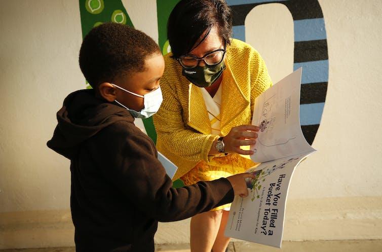 Kindergartener discusses picture book with school administrator
