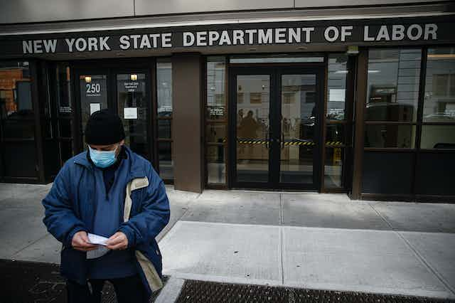 A man wearing a mask walks away from the New York State Department of Labor.