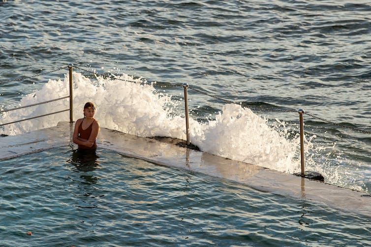 Woman sitting in an ocean pool.