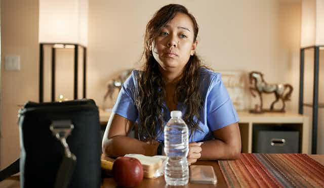 Exhausted nurse sits at a table in front of her packed lunch and handbag.