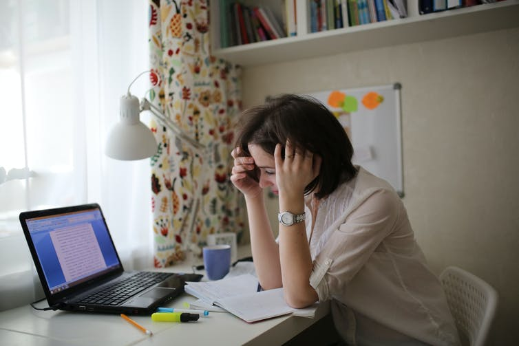 tired woman with laptop open in front of her rests head on hands at desk