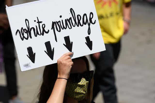 A woman in a green face mask and shades holds a black and white placard reading 'White Privilege' with arrows pointing downward to indicate the woman holding the poster