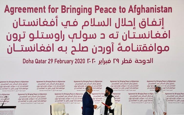 Homme en costume sert la main d'un taliban afghan en turban