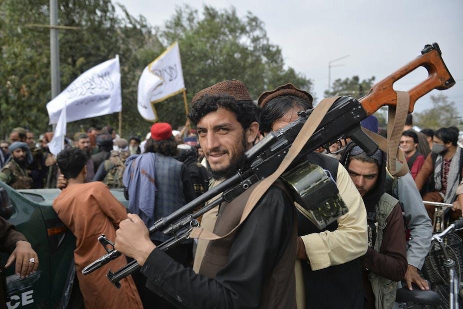 Soldat taliban en civil équipé d'une mitrailleuse sourit au milieu d'une foule.