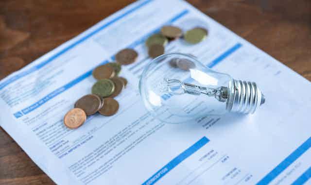 Una bombilla y unas monedas sobre una factura de luz.