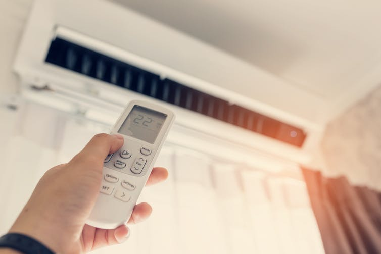 hand holds remote control at air conditioner
