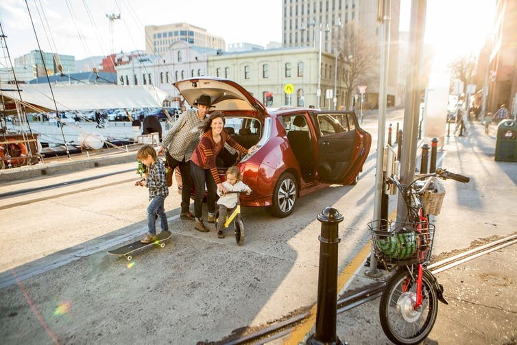 family unloads boot of electric car